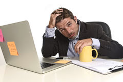 Exhausted businessman suffering stress at office computer desk overwhelmed tired. Tired and frustrated businessman desperate face expression suffering stress and Stock Photography