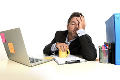 Exhausted businessman suffering stress at office computer desk overwhelmed tired. Tired and frustrated businessman desperate face expression suffering stress Royalty Free Stock Photography