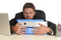 Exhausted businessman suffering stress at office computer desk. Tired and frustrated businessman desperate face expression suffering stress at office computer Stock Photography