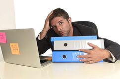 Exhausted businessman suffering stress at office computer desk. Tired and frustrated businessman desperate face expression suffering stress at office computer Stock Photos