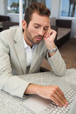 Exhausted businessman working with his laptop at table Royalty Free Stock Image