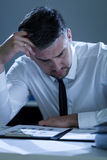 Exhausted businessman working at office Stock Images