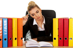 Exhausted businesswoman with binders behind the desk Royalty Free Stock Images