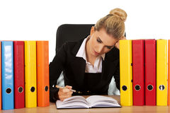 Exhausted businesswoman with binders behind the desk Stock Images
