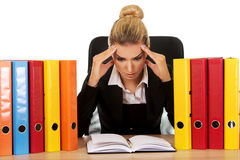 Exhausted businesswoman with binders behind the desk Stock Photos