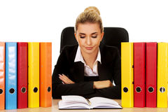 Exhausted businesswoman with binders behind the desk Royalty Free Stock Photo