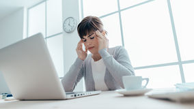 Exhausted businesswoman with headache. Exhausted young woman working at office desk touching her temples, she is having a bad headache, stressful life and Stock Photography