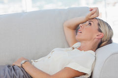 Exhausted businesswoman lying on sofa Stock Image