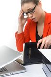 Exhausted businesswoman reading bible at table. Girl trying to solve problem in holy scripture Royalty Free Stock Images
