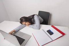 Exhausted businesswoman sleeping at office desk Stock Photos
