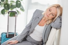 Exhausted businesswoman waiting for trip. Exhausted businesswoman sleeping while waiting for trip Royalty Free Stock Image