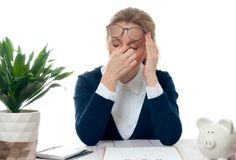 Businesswoman working at office desk is having an headache. Exhausted businesswoman working at office desk is having an headache, too much work Royalty Free Stock Photography