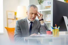Exhausted busy businessman closing his eyes and rubbing temples royalty free stock image