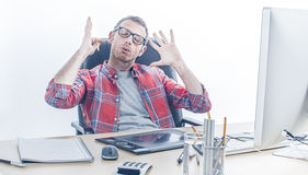 Exhausted casual man with eyeglasses being sick of working. At his computer desk, raising his hands for exasperation and stress, white background Stock Photos
