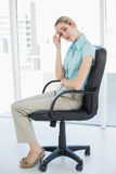 Exhausted classy businesswoman sitting on her swivel chair Stock Photo