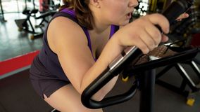 Exhausted corpulent female sitting on stationary bike and suffering from dyspnea stock images