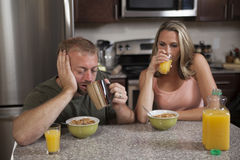 Exhausted couple has breakfast. Exhausted couple at the breakfast table drinking coffee and orange juice royalty free stock photo