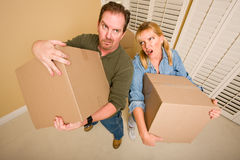 Exhausted Couple Holding Moving Boxes Royalty Free Stock Image