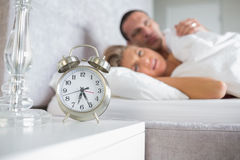 Exhausted couple looking at alarm clock Stock Photography