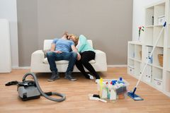 Exhausted couple on sofa in living room. Exhausted Couple Resting On Sofa In Living Room Royalty Free Stock Images
