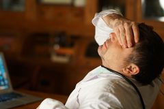 Exhausted doctor. Tired overworked doctor sitting at desk and covering his eyes Stock Image