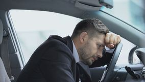 Exhausted driver leaning on steering wheel to relax, stressful job, overworking