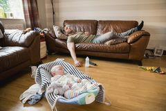 Father and Son Sleeping at Home. Exhausted father having a nap on the sofa while her newborn child has a sleep stock photo