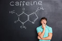 Exhausted fatigued man yawning over chalkboard with drawn caffeine molecule Royalty Free Stock Photo