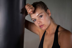 Exhausted female boxer leaning on punching bag. In fitness studio Royalty Free Stock Images
