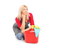 Exhausted female cleaner sitting next to a bucket Stock Photo