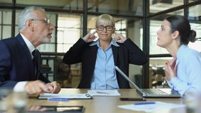 Exhausted female covering ears looking arguing coworkers, stressful atmosphere. Stock footage stock footage