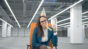 Exhausted female employee is blowing a cracker. 4K stock video