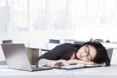 Exhausted female entrepreneur napping in office. Portrait of female worker wearing formal suit relaxing and sleeping in office with laptop in office Royalty Free Stock Photos