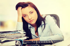 Exhausted female filling out tax forms Stock Photo