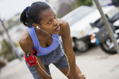 Exhausted female jogger stopping for breath on pavement, leaning on knees, listening to MP3 player strapped to arm, focus on foreg Stock Photography