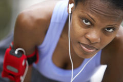 Exhausted female jogger wearing sports vest, leaning forwards, listening to MP3 player strapped to arm, close-up, portrait (differ Stock Photos