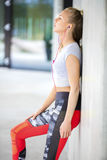 Exhausted Fit Woman In Sportswear Leaning On Wall Royalty Free Stock Photos