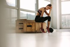 Exhausted fitness woman resting at gym Royalty Free Stock Images