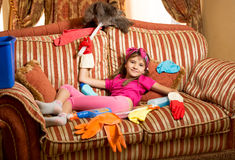 Exhausted girl relaxing on sofa after cleaning house. Funny photo of exhausted girl relaxing on sofa after cleaning house Stock Photo