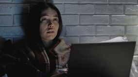 Exhausted girl working on laptop in bed at night, showing help word sign stock video