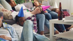 Exhausted girls and guys sleeping on floor and sofa after party in apartment. Exhausted girls and guys in bright hats are sleeping on floor and sofa after party stock footage