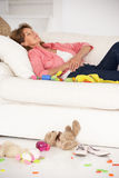Exhausted grandmother enjoying a rest on sofa Stock Photos