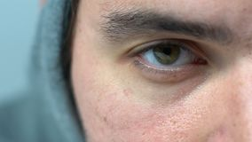 Exhausted green-eyed man in hood blinking looking into camera, macro closeup. Stock footage stock video