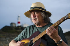 Exhausted guitarist at lighthouse concert Stock Photos