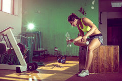 Exhausted gym girl drinking water. Stock Photos