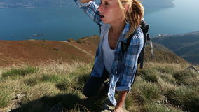 Exhausted hiker reaches top of mountain stock footage