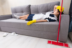 Exhausted housekeeper relaxing on the job Royalty Free Stock Images