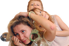 Exhausted housewife. Portrait of an exhausted housewife holding a ladle, chained to pots with handcuffs with two kids Stock Image