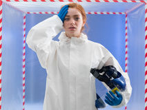 Exhausted or infected biohazard scientist. Exhausted or infected female biohazard scientist dressed in a biohazard suit holding her helmet mask in one hand and Royalty Free Stock Images