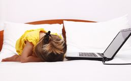 Exhausted kid who sleep near a laptop Royalty Free Stock Photos